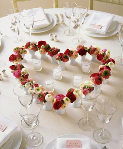 muchos floreros forman un corazón sobre una mesa