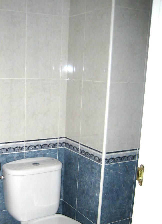 baño con azulejos antes de pintar
